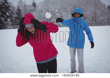 Smiling man throwing snowball at woman
