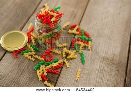 Glass jar filled with tri-colored rotini pasta on wooden background