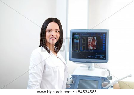 Young female doctor smiling happily to the camera posing at her office near ultrasound scanning machine copyspace medical industry technology modern equipment diagnostics sonography healthcare.