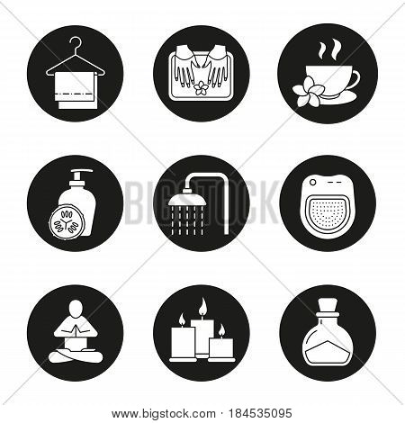 Spa salon icons set. Towels on clothes hanger, yoga pose, cucumber lotion, shower, herbal teacup, candles, salt bottle, spa salon bath. Vector white silhouettes illustrations in black circles