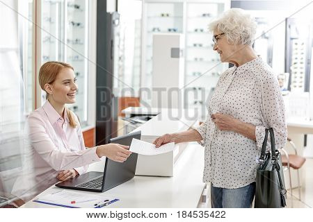Joyful old lady is giving document to receptionist of eyeglasses store. They are looking at each other with smile