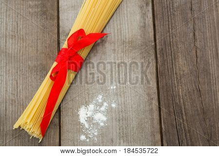 Bundle of raw spaghetti and flour on wooden surface