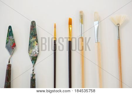 Palette knives and paint brushes arranged in a row on white background