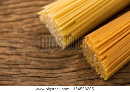 Bundles of raw spaghetti on wooden surface