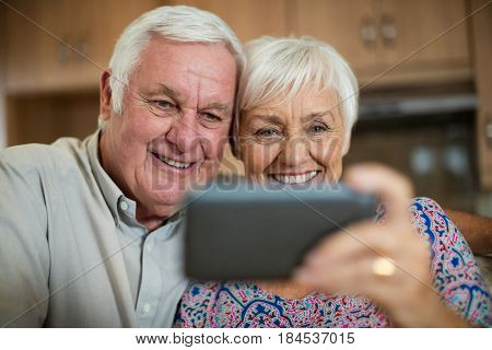 Senior woman taking selfie from mobile phone in kitchen at home