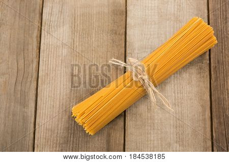 Bundle of raw spaghetti tied with rope on wooden surface