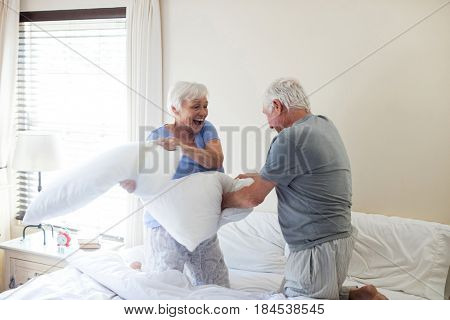 Senior couple having pillow fight on bed in bedroom