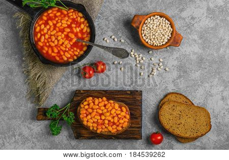 Braised beans in tomato sauce in cast iron pan. Vegetarian sandwiches with bean. Open sandwiches with bread, stewed white beans. Raw white beans, pieces of rye bread for sandwiches. Top view.