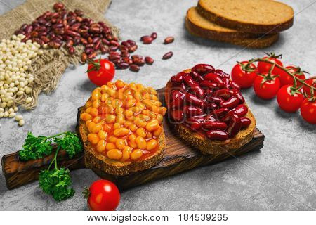 Braised beans in tomato sauce on vegetarian sandwiches with bean. Open sandwiches with bread stewed white and red beans. Raw beans pieces of rye bread for sandwiches. Gray stone background.