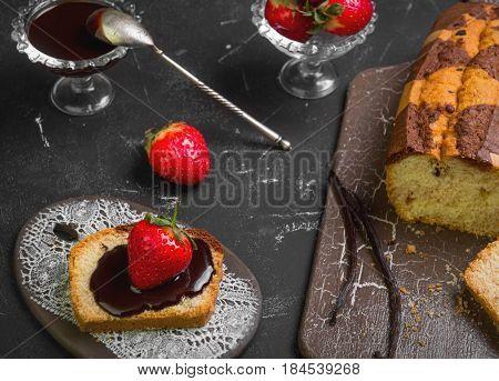 Breakfast strawberry bruschetta with chocolate sauce. Healthy fruit sandwich with strawberry. Ingredients for sandwiches biscuit bread fresh strawberries chocolate. Dark black background.