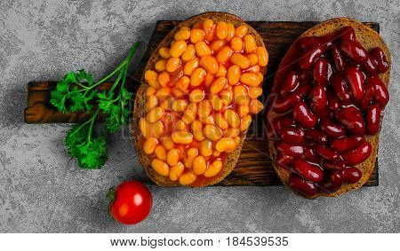 Braised beans in tomato sauce on vegetarian sandwiches with bean. Open sandwiches with bread stewed white and red beans. Top view.