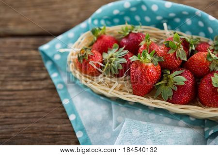 Fresh strawberries in wicker tray on wooden table