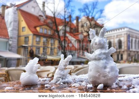 Hares of snow on the table in the city caf on the Livu square in Riga on a Sunny day in early spring