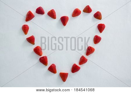 Red strawberries forming a heart shape on white background