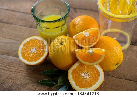Close-up of oranges with glasses of juice and juicer on wooden table