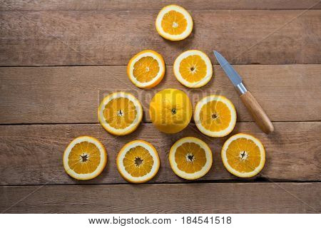Overhead of oranges forming a triangle shape on wooden table