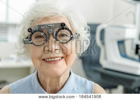 Happy mature lady wearing strange spectacles is looking at camera with bright smile. Portrait