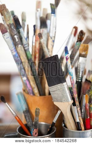 Set of paint brushes in a jar and mug on wooden table