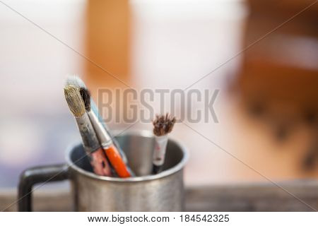 Set of paint brushes in a mug on wooden table