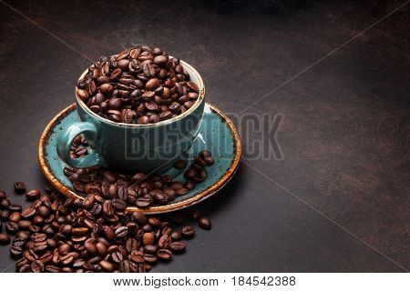 Coffee cup with beans on stone background. With copy space for your text