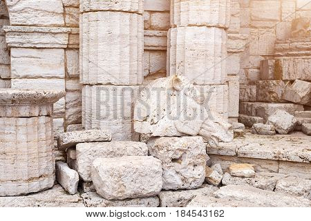 Classical old greek columns and wall background with stone floor and sculpture of a horse head.