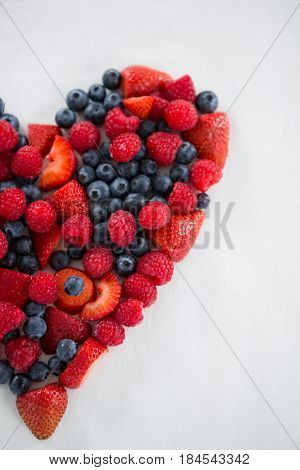 Close-up of various fruits forming a heart shape against white background