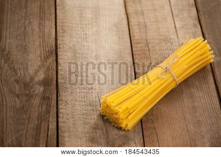 Bundle of raw spaghetti tied with rope on wooden background