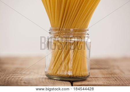 Bundle of raw spaghetti in glass jar on wooden background