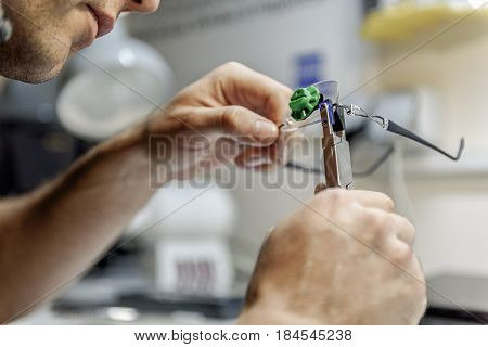 Man is using special tool in order to attach necessary details to lens. Close up of male hands