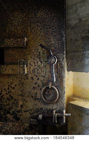 Rusty old heavy metal door in an underground bunker at Point du Hoc France.