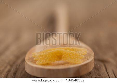 Farfalle pasta in wooden spoon on white background