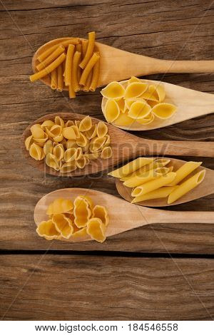 Spoons filled with varieties of pasta on wooden background