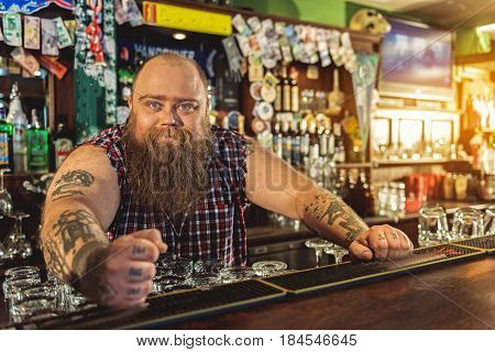 It is my bar. Portrait of outgoing fat male leaning on worktop in alehouse. He looking at camera