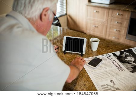 Senior man looking at digital tablet in the kitchen at home