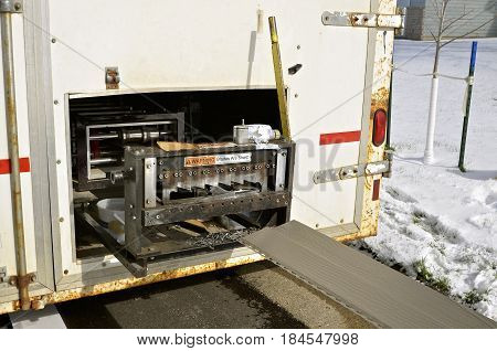 Located inside the back of a truck is a machine for cutting metal steel siding for the exterior of a building.