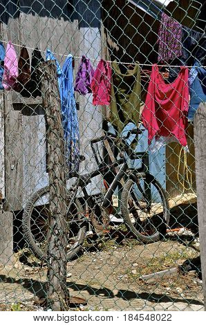 A bicycle and drying clothes are on the inside of a fence in a Mexican village.