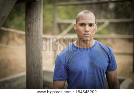 Portrait of determined man standing during obstacle course in boot camp