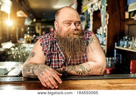 Portrait of pensive fat bartender working in tap-room. He waiting for visitors