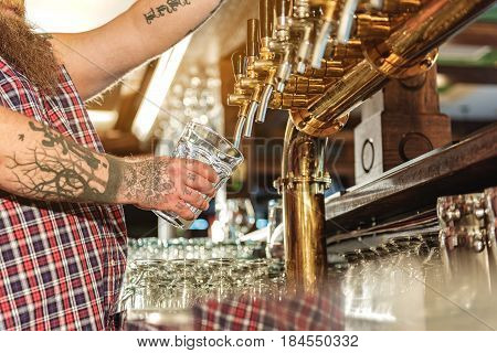 Bearded male bartender pouring beer from tap in big glass in boozer