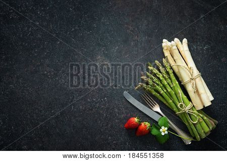 Fresh green and white asparagus with strawberries and silverware on dark background