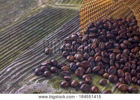 Coffee beans in coffee bag on old green wooden surface