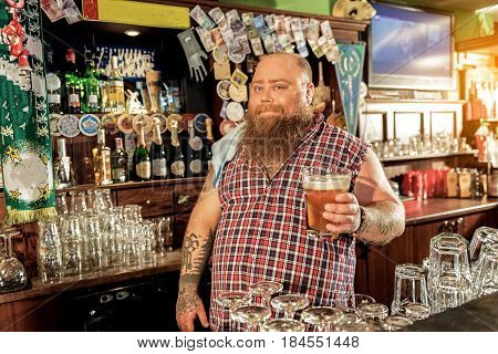 Fat man expressing gladness while drinking cold beer in bar
