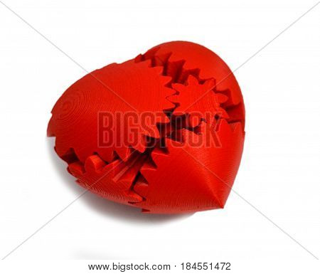 Objects printed by 3d printer Isolated on white background. Bright colorful object. Heart of red color several parts. Automatic three dimensional 3d printer performs plastic modeling in laboratory.