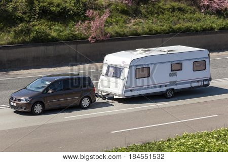 Frankfurt Germany - March 30 2017: Volkswagen Touran towing a caravan on the highway in Germany