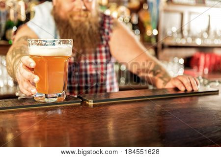 Here is your cold alcohol beverage. Focus on close up male arm giving glass of alcohol in pub