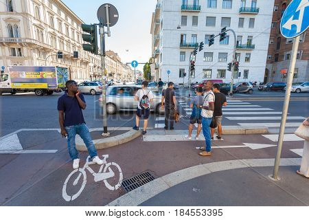 MILAN ITALY - September 06 2016: Pedestrians are waiting the green light of traffic light on the crossroad on Avenue Buenos Aires (Corso Buenos Aires) and street Bastioni di Porta Venezia where there is a bicycle lane for bicyclists