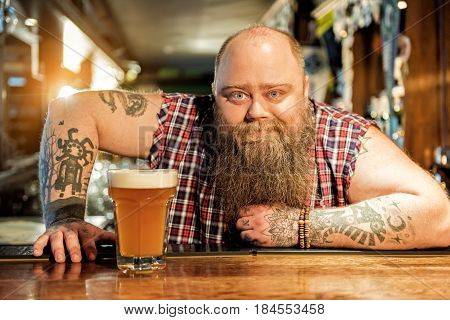 It is my glass of beer. Portrait of brutal bearded male expressing cheerfulness while leaning on workplace in pub