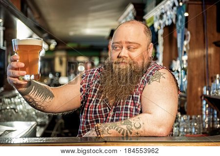 This attractive nectar. Obese man showing gladness while he tasting ale in pub