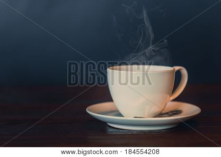 White Hot Coffee Cup On Wood Table With Smoke Vapor On Dark Background Vintage Color Tone.