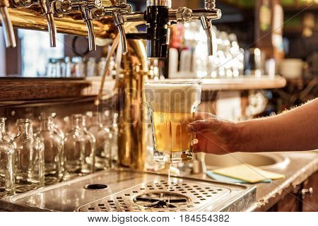 Focus on close up man hand filling glass of cold alcohol beverage from special equipment in pub